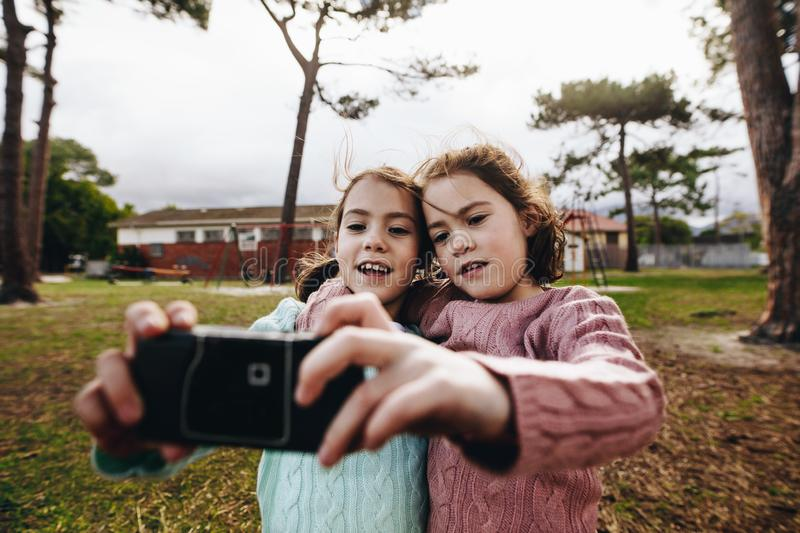 Identical twin girls taking selfie with old camera at park royalty free stock photography