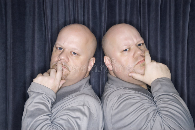 Identical twin men. Caucasian bald identical twin men standing back to back and looking at viewer with hands to mouth royalty free stock images