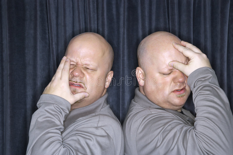 Identical twin men. Caucasian bald identical twin men standing back to back and grimicing with hands to head stock photo