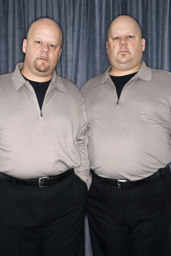 Identical twin men. Caucasian bald identical twin mid adult men standing together looking at viewer royalty free stock photo