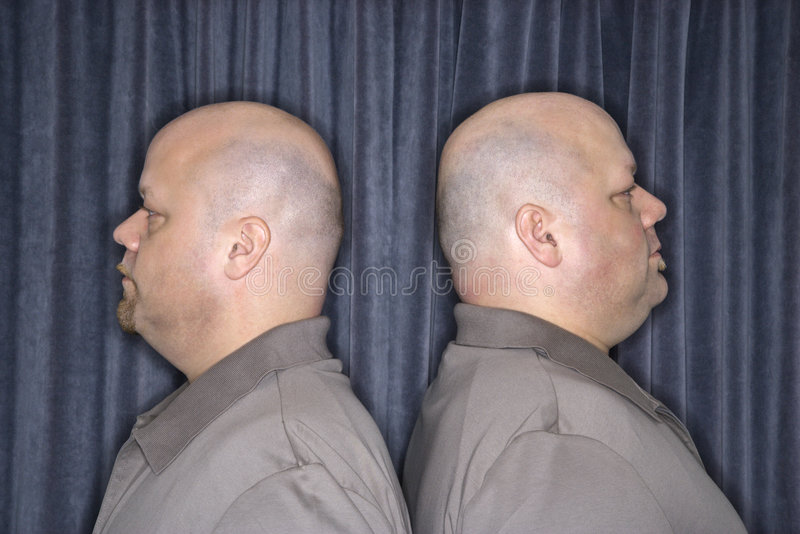 Identical twin men. Profile of Caucasian bald identical twin mid adult men standing back to back royalty free stock photography