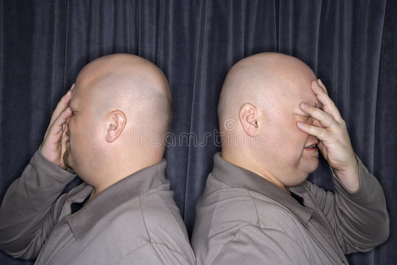 Identical twin men. Profile of Caucasian bald identical twin men standing back to back and grimicing with hands to head royalty free stock photos