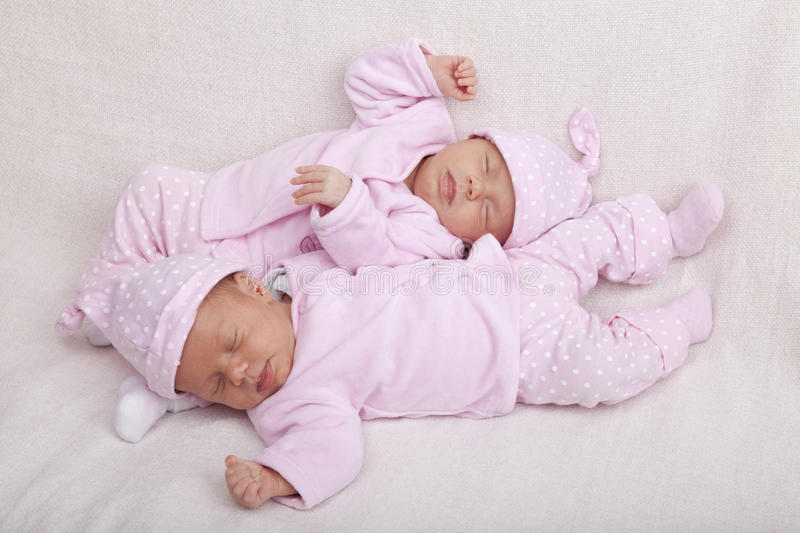 Identical twin sisters. Studio-shot of identical twin girls sleeping on a sofa royalty free stock photography