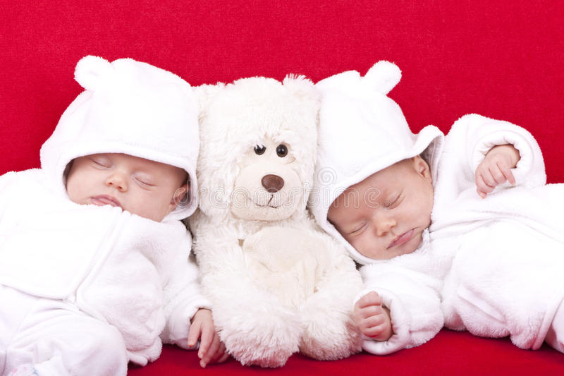 Identical twin sisters. Studio-shot of identical ( similar ) twin baby sisters resting and sleeping on a red sofa stock photography