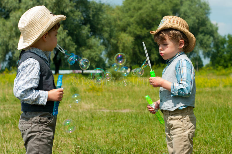 Identical twins blow soap bubbles stock photography