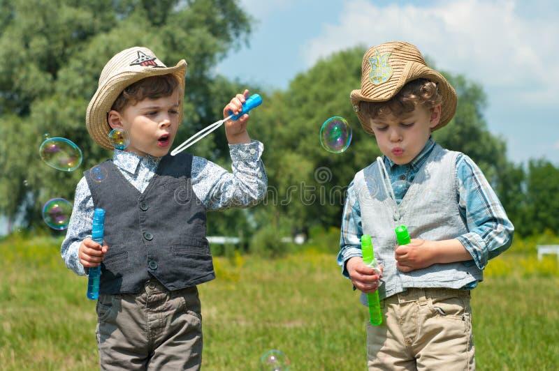 Identical twins blow soap bubbles stock photo