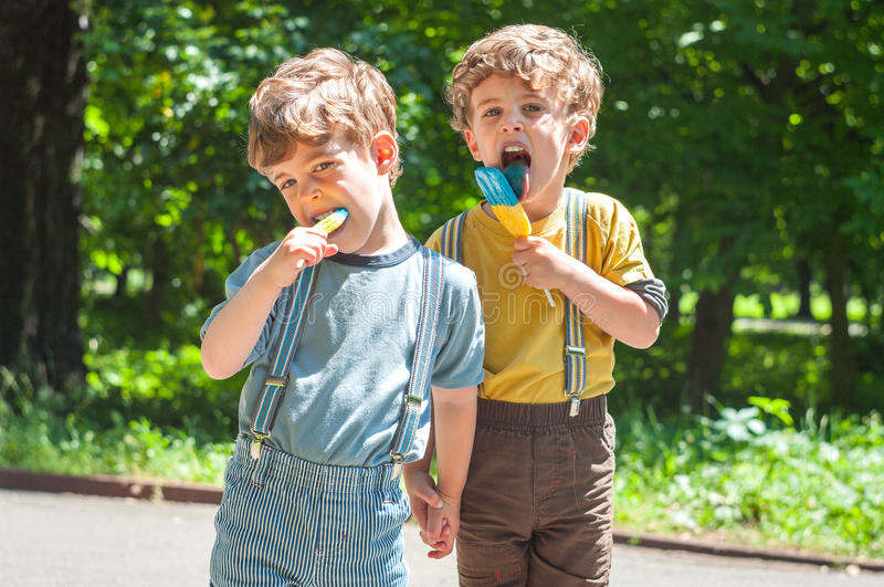 Identical twins eat lollies stock photography