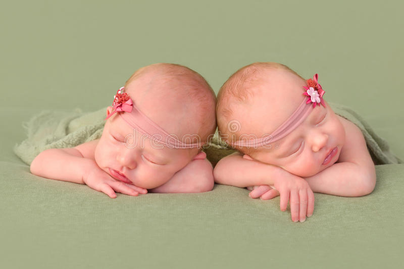 Identical twins with headbands. 3 weeks old identical twin girls sleeping on a green backdrop stock photo