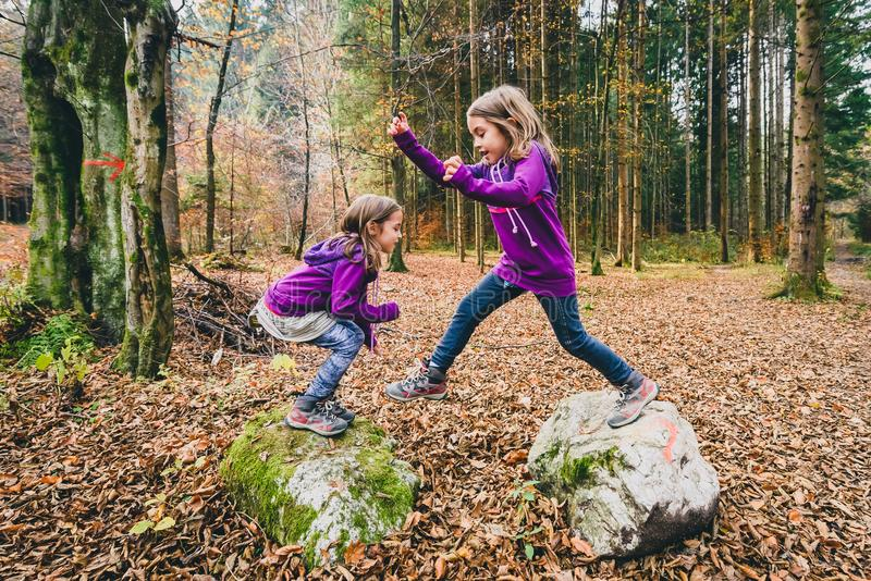 Identical twins are jumping from rocks in forest on hiking. royalty free stock image