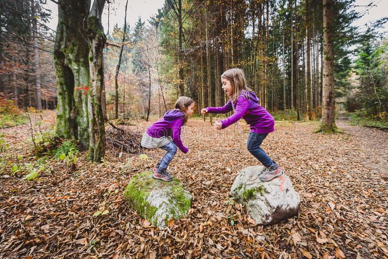 Identical twins are jumping from rocks in forest on hiking. stock images