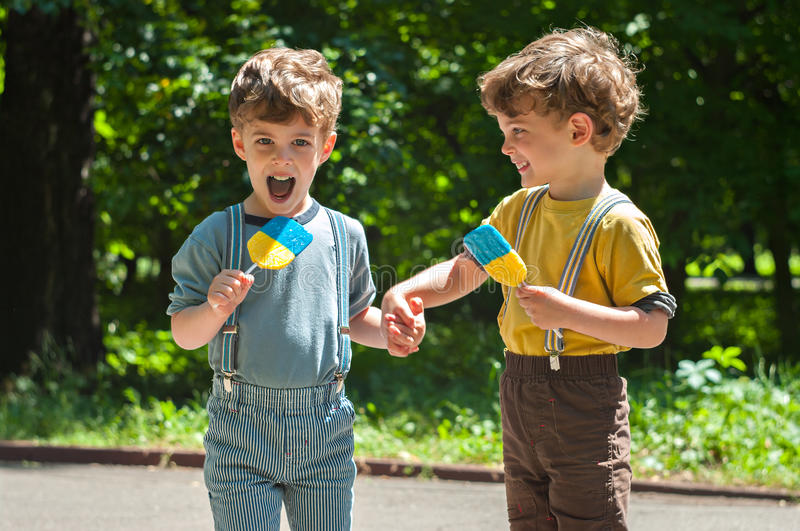 Identical twins with lollipops. Three year old identical twins hold hands. They are holding the candy in the colors of the Ukrainian flag. Summertime stock photography