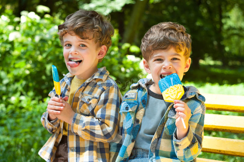 Identical twins with lollipops royalty free stock photos