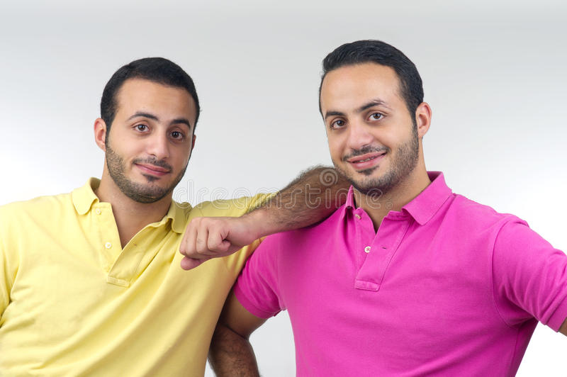 Identical twins portraits shot isolated. On a gray background stock photos