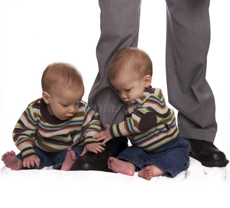 Identieke tweelingbabyjongens die dads benen houden royalty-vrije stock fotografie