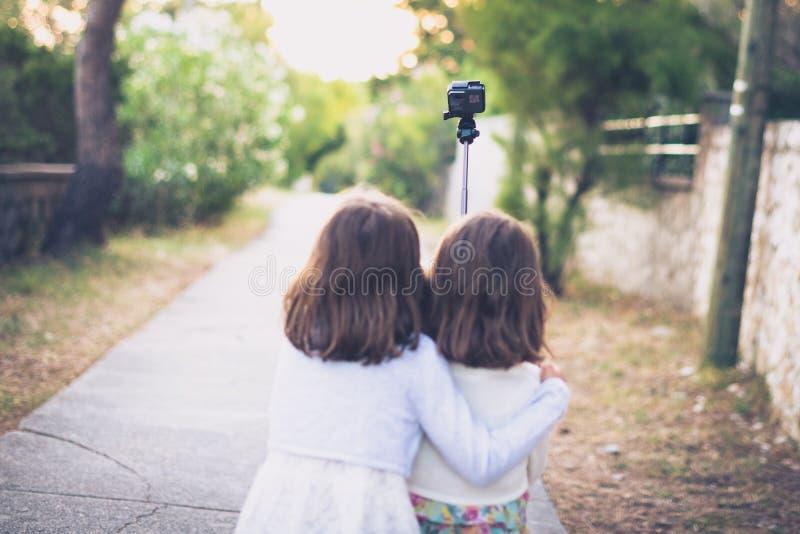 Identieke tweelingzusters die en selfie met actieca lopen nemen stock foto's