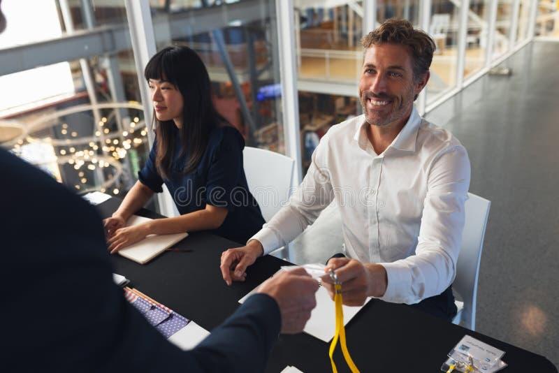 Identificação de doação executiva masculina do empregado ao homem de negócios na tabela do registro da conferência fotografia de stock
