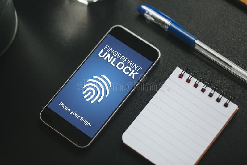 Identifiera med fingeravtryck att låsa i en mobiltelefonskärm över en svart affärstabell upp royaltyfria foton
