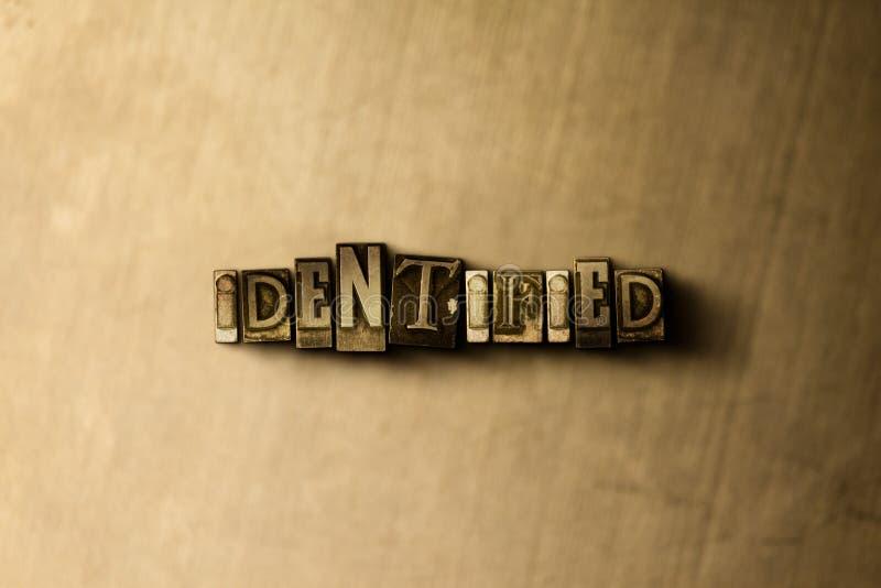 IDENTIFIERAT - närbild av det typsatta ordet för grungy tappning på metallbakgrunden arkivfoto