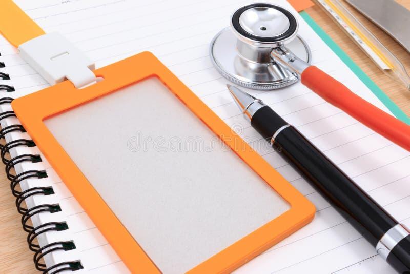 Identifikations-Kartenhalter, Stift, Thermometer und Stethoskop mit leerem Notizbuch lizenzfreie stockfotografie