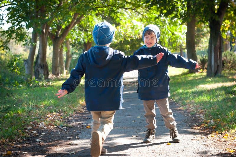 Identisk körning för tvilling- bröder som omfamnar sig arkivfoto