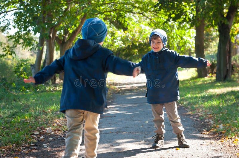 Identisk körning för tvilling- bröder som omfamnar sig fotografering för bildbyråer
