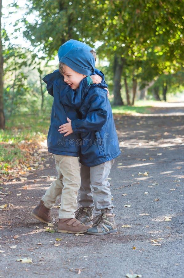 Identisk omfamning för tvilling- bröder royaltyfri foto