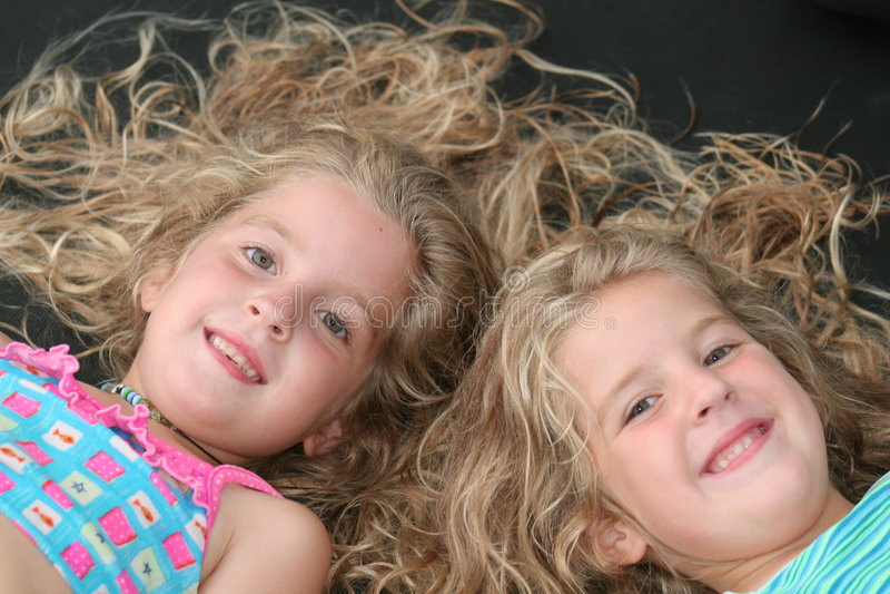 identiska barn kopplar samman arkivfoto