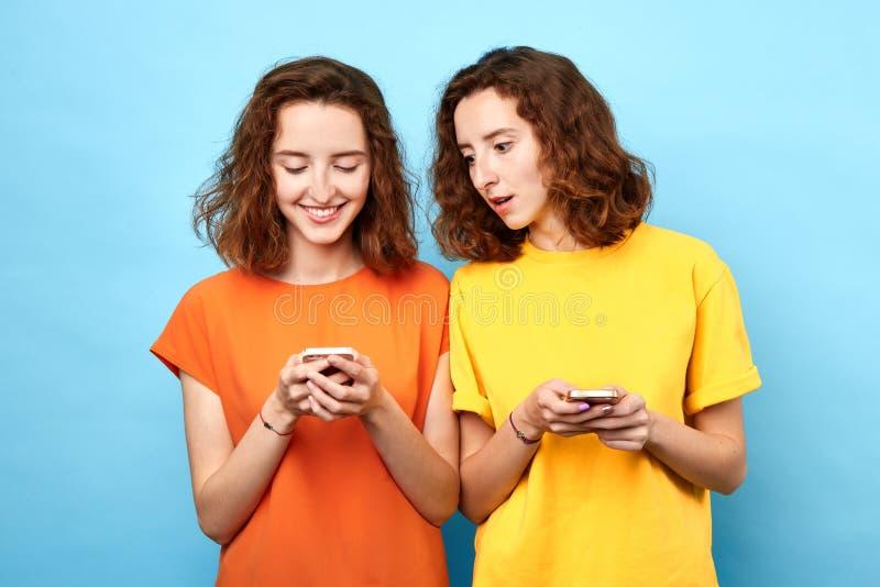 Identiska två kopplar samman att rymma mobiltelefoner som gör en påringning royaltyfri foto