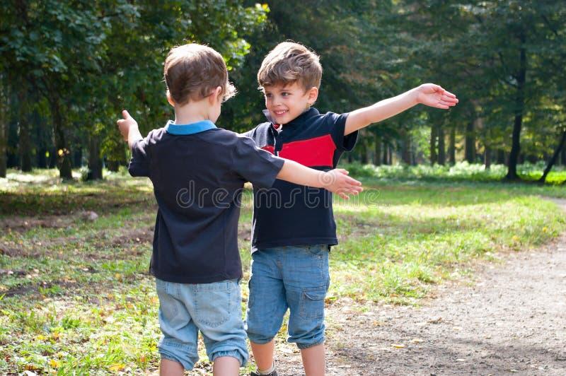 Identiska tvilling- bröder som är klara att omfamna arkivfoton