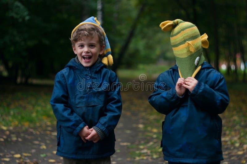 Identiska tvilling- bröder som skojar med hatten royaltyfri foto