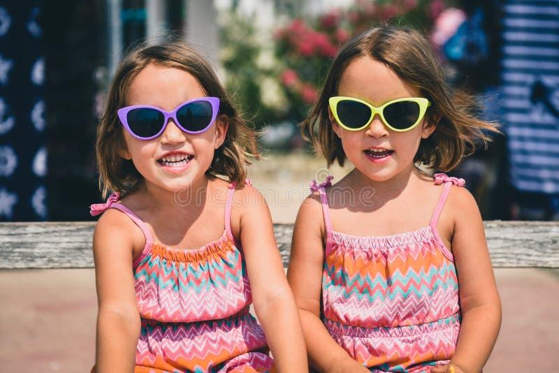 Identiska tvilling- flickor på sommarsemestern som poserar för kamera arkivbild