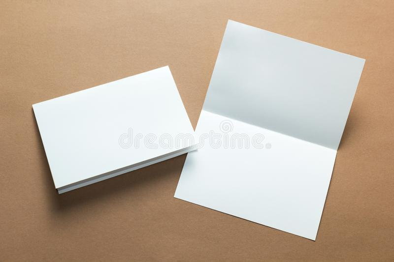 Identity design, corporate templates, Blank A5 Flyer, blank white folding paper flyer  on brown background, mock-up.  royalty free stock photography