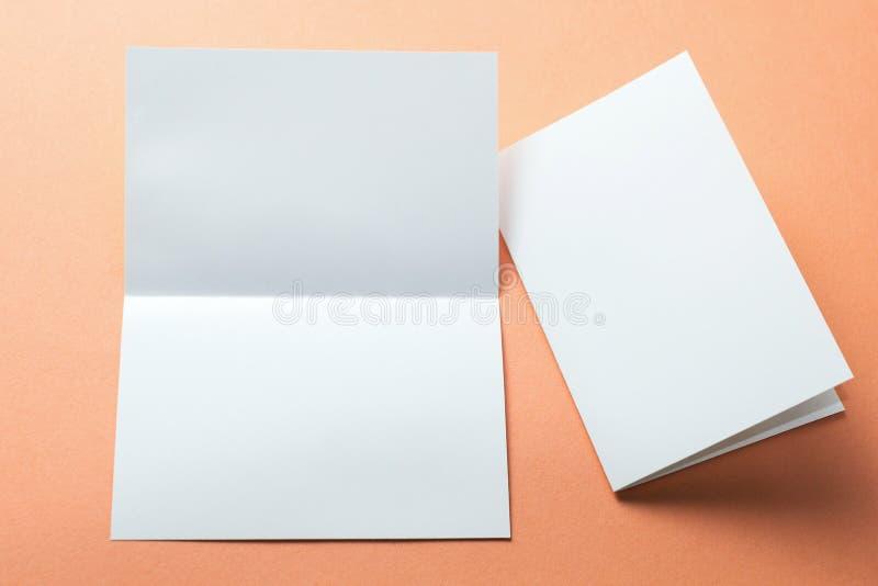 Identity design, corporate templates, company style, blank white folding paper flyer isolated on orange background, mock-up.  royalty free stock photo