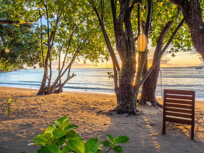 Idilic tropical beach. Pulisan, North Sulawesi. Sunrise in paradise. Rustic lounger in foreground of deserted tropical beach in Pulisan region of North Sulawesi royalty free stock photography