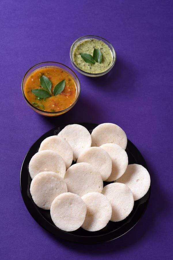 Idli用在紫罗兰色背景,印地安盘的水鹿和椰子酸辣调味品 免版税库存图片