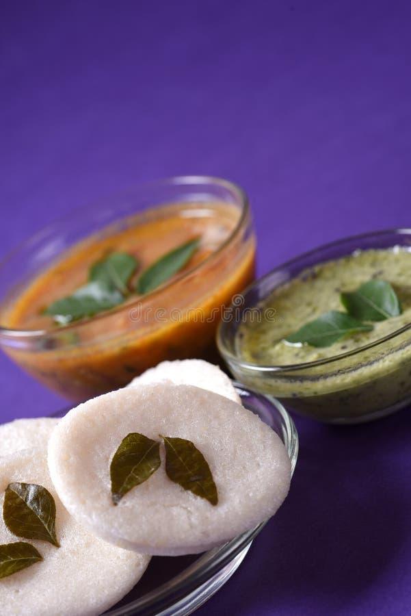 Idli com chutney do Sambar e do coco no fundo violeta, prato indiano imagens de stock royalty free