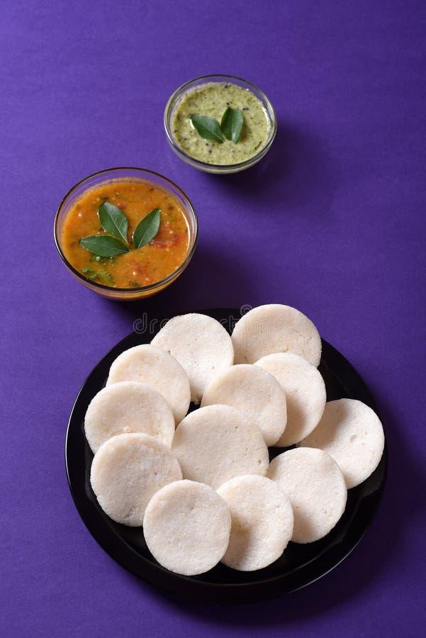 Idli met Sambar en kokosnotenchutney op violette achtergrond, Indische Schotel stock afbeelding