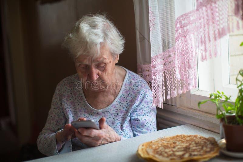 A idosa senta-se com um smartphone nas mãos de casa Ajuda fotos de stock royalty free