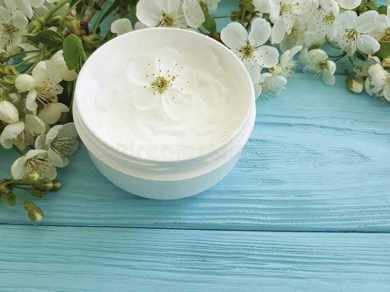 Idratante cosmetico crema che nutrisce la ciliegia sbocciante sana di trattamento organico su un fondo di legno blu fotografie stock