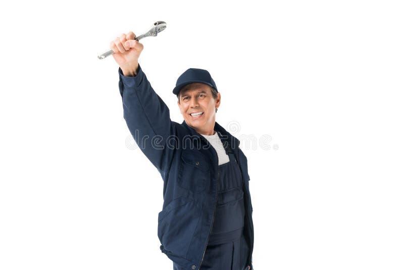 Idraulico bello in chiave inglese uniforme della tenuta fotografia stock libera da diritti