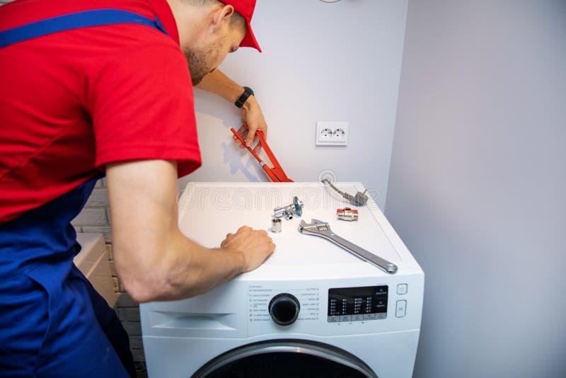 Idraulico che installa lavatrice fotografia stock libera da diritti
