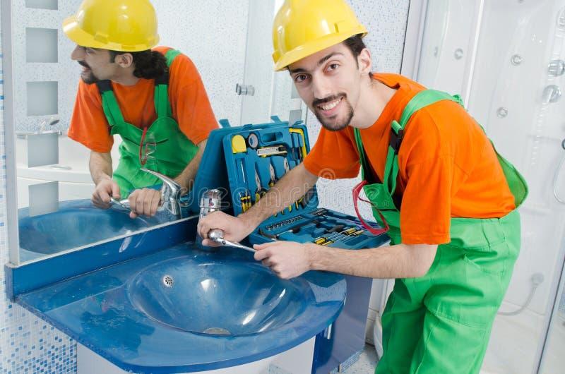 Idraulico che lavora nella stanza da bagno immagini stock libere da diritti
