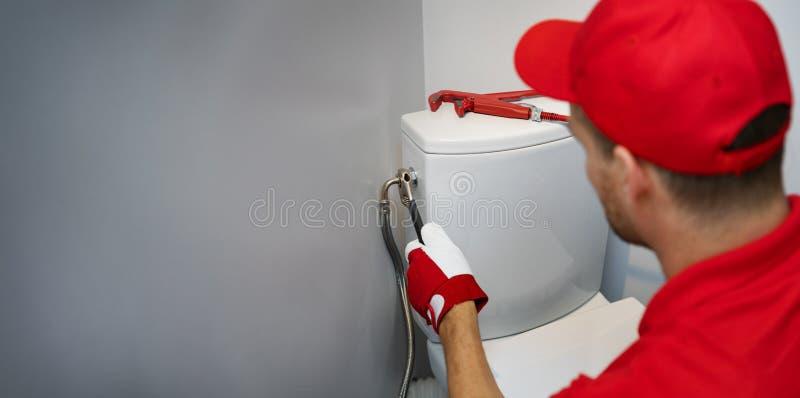 Idraulico che lavora nella toilette che installa tubatura dell'acqua allo spazio della copia del carro armato del wc fotografia stock libera da diritti
