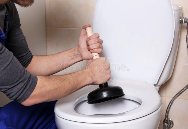 Idraulico che ripara toilette fotografia stock