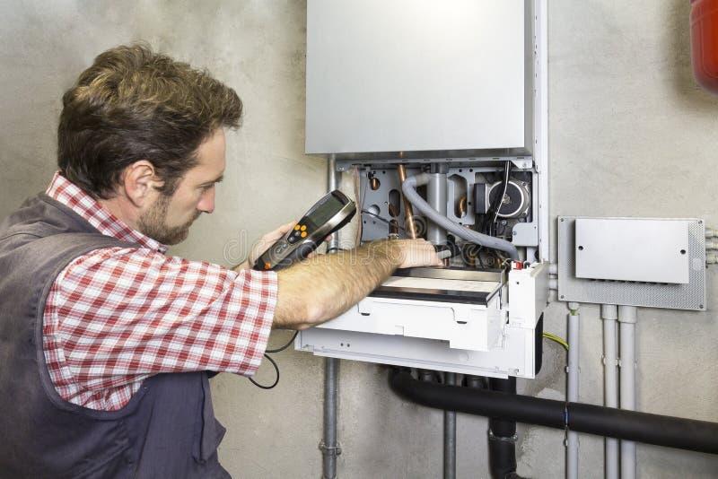 Idraulico che ripara una caldaia di condensazione fotografie stock