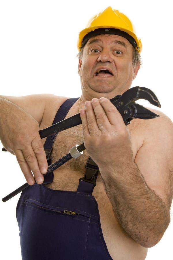 Idraulico con la chiave di tubo ed il casco di sicurezza fotografia stock