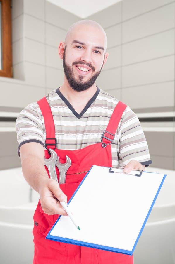 Idraulico maschio sorridente che dà la lavagna per appunti fotografia stock libera da diritti