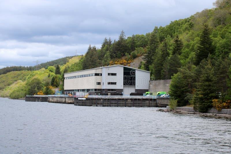 Idro stazione elettrica sulla riva del lago fotografia stock