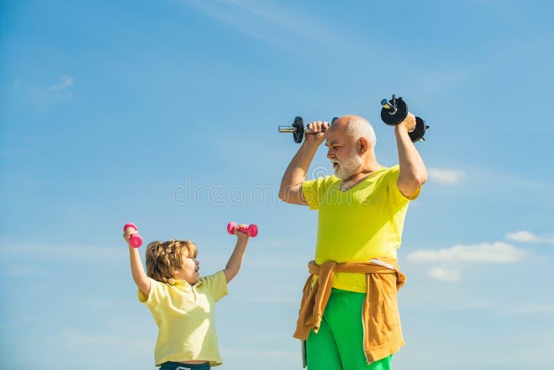 Idrott för barn Pojken gör övningar för att utveckla muskler Farfar hjälper barn att träna med dumbbell royaltyfri bild