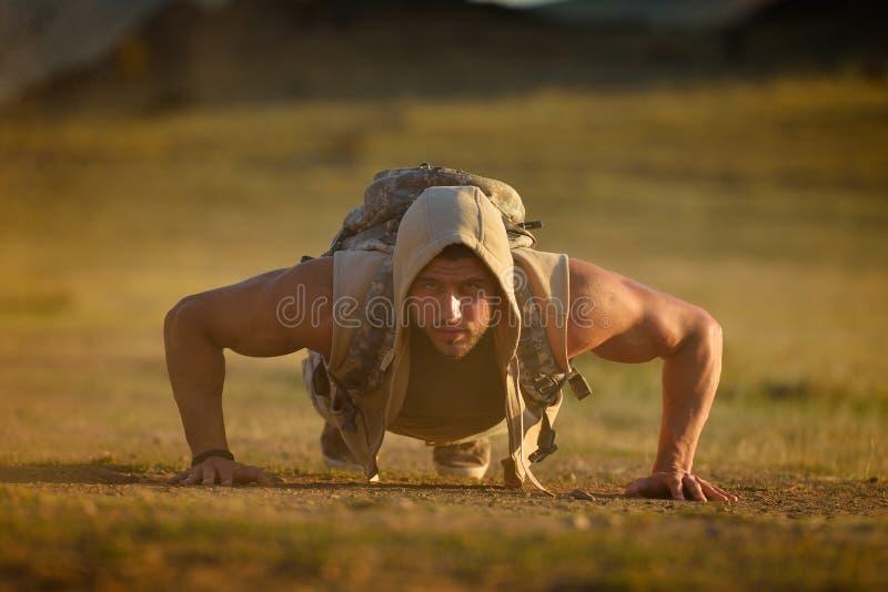 Idrotts- öva för ung man som är utomhus- på dammigt fält royaltyfri foto